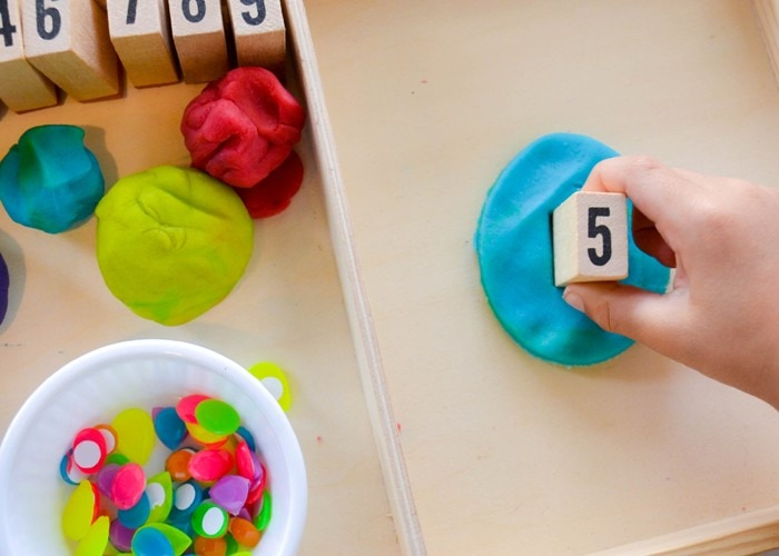 Easter Egg Stamp and Count Playdough Math: Children can decorate Easter eggs as they work on one-to-one correspondence, fine motor skills, and number recognition. (#math #preschool #easteractivity #easteregg)